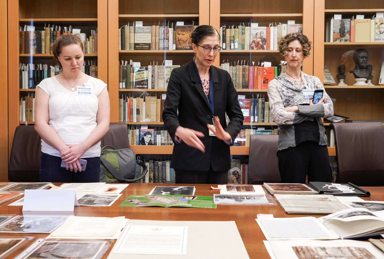 Theresa Salazar, center, The Bancroft Library's curator for Western Americana, looks over items being considered for the Sustaining Grandeur exhibit with guests in March.