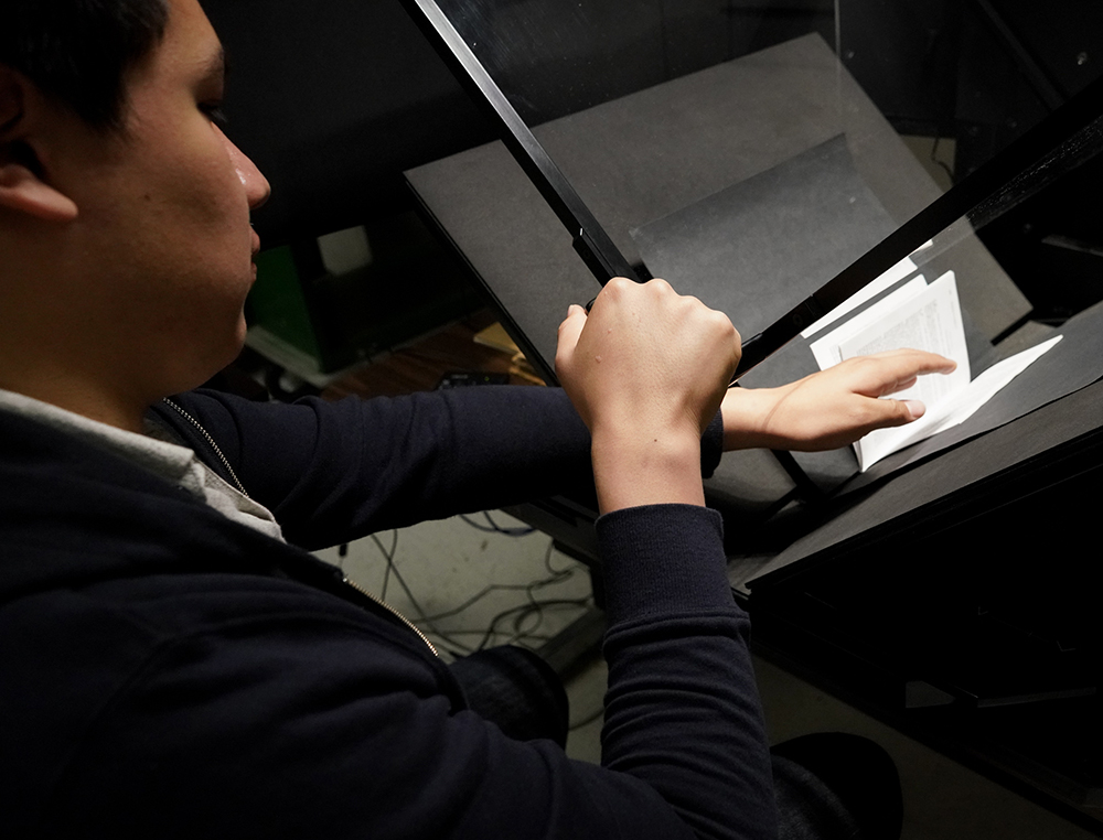 Employee Marco Perez digitizes The Selfish Gene by Richard Dawkins as part of the Alternative Media Services program.