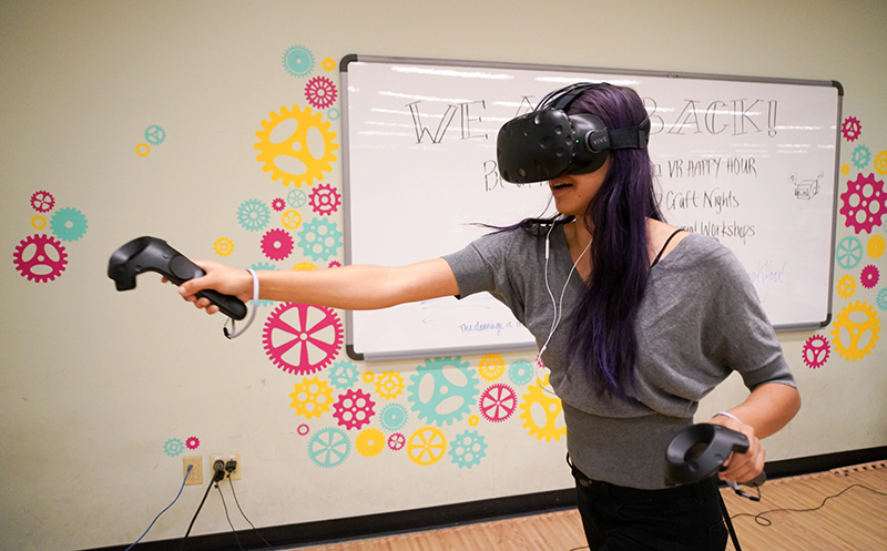 A participant tries out a virtual reality game in Moffitt Library during a Makerspace event on April 20, 2018.